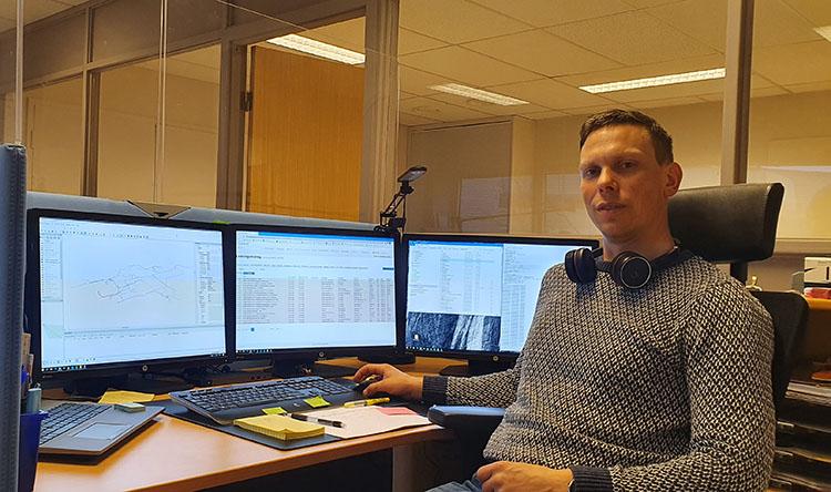 Mann foran dataskjermer på kontor