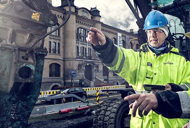 Mann med hjelm som peker på et anleggsområde